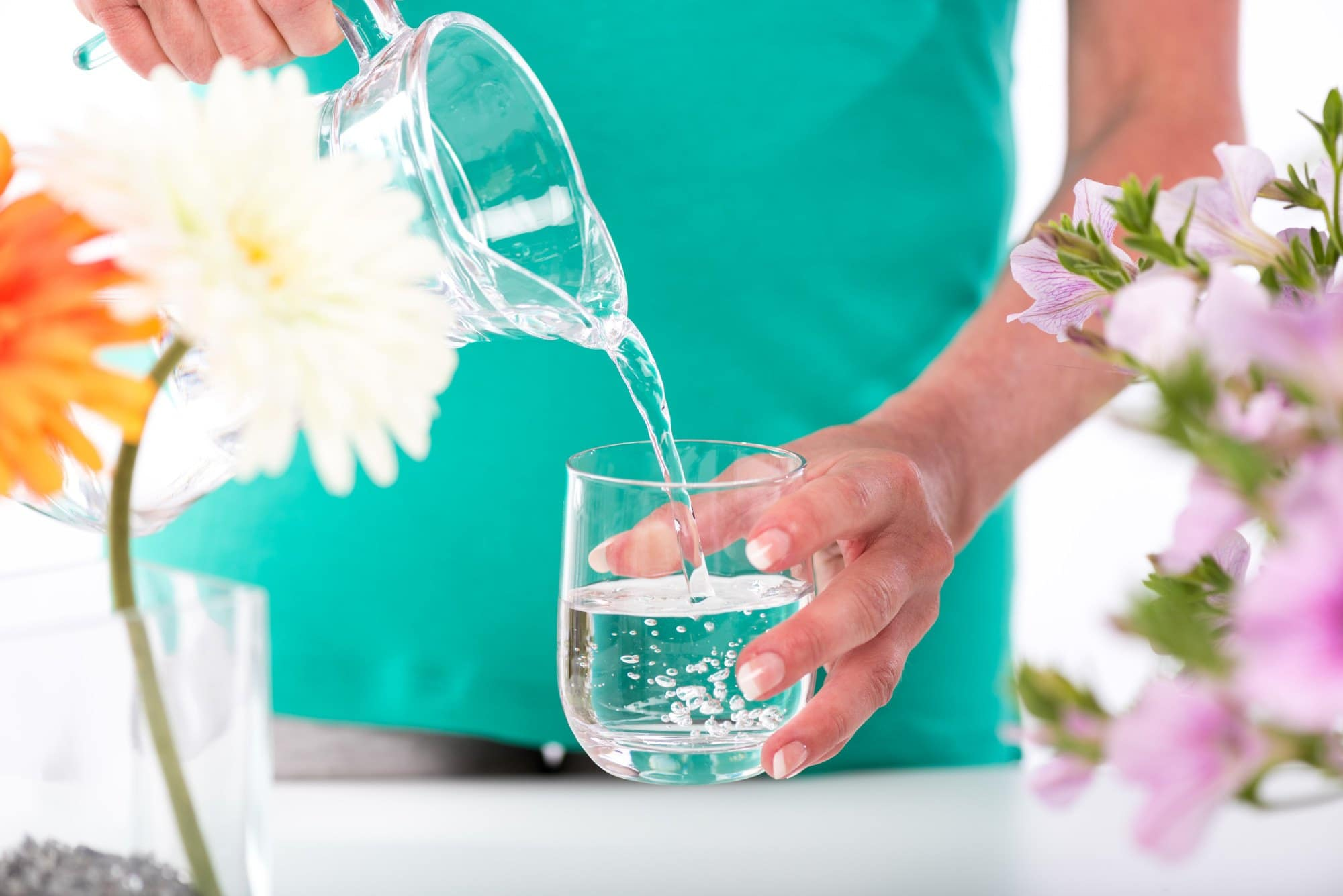 a woman pouring a glass of water for hydration